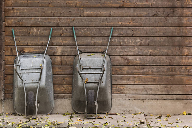 Two wheelbarrows leaning against the wall of a shed by Melanie Kintz for Stocksy United