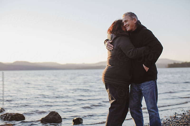 Happy, mature couple enjoying hugging each other at the beach at sunset by Rob and Julia Campbell for Stocksy United