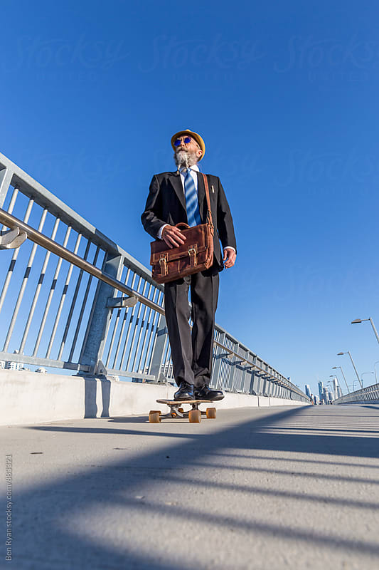 Low angle view of alternative elderly businessman in suit skateboarding across bridge with tall buildings in background by Ben Ryan for Stocksy United
