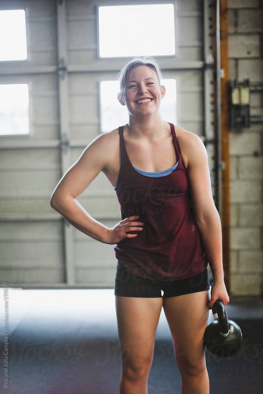 Happy young woman holding kettle bell in gritty workout gym by Rob and Julia Campbell for Stocksy United
