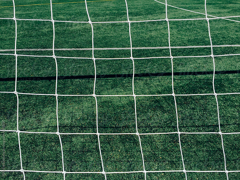 Netting from soccer goal and green sports turf by Paul Edmondson for Stocksy United