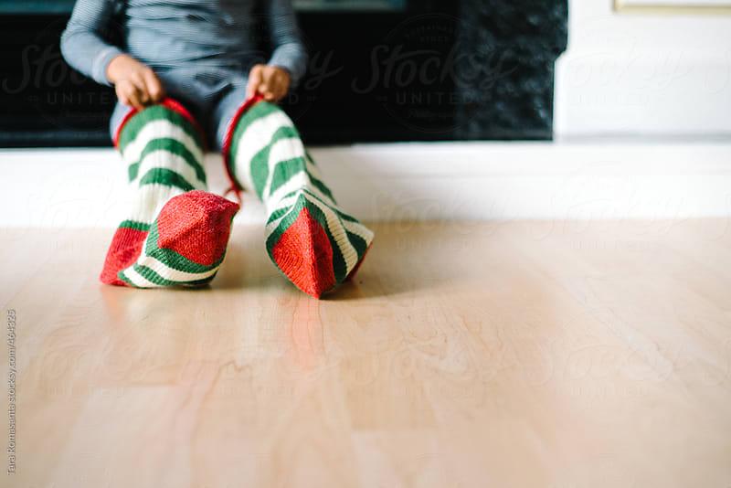 child wears Christmas stockings  by Tara Romasanta for Stocksy United