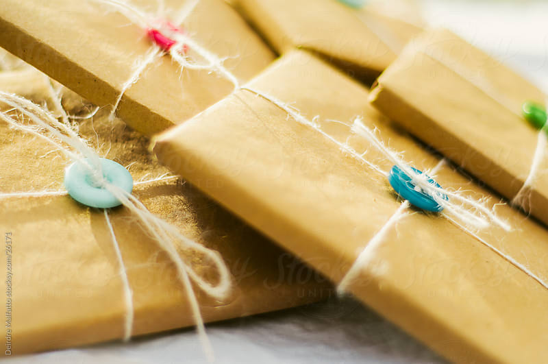 brown paper packages tied up in string by Deirdre Malfatto for Stocksy United