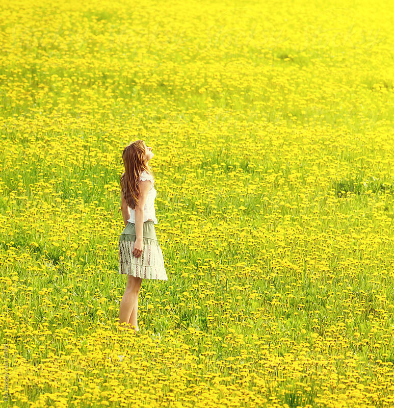 Young woman in summer dress enjoying standing in spring dandelion meadow by Ilya for Stocksy United