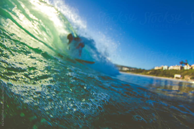 Out of focus picture of surfer riding a wave. by Robert Zaleski for Stocksy United