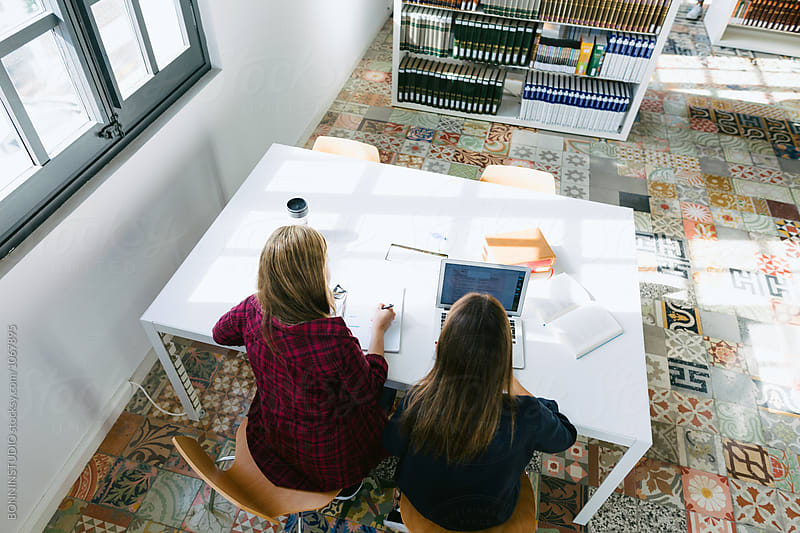 Overhead of two college students studying in a library. by BONNINSTUDIO for Stocksy United