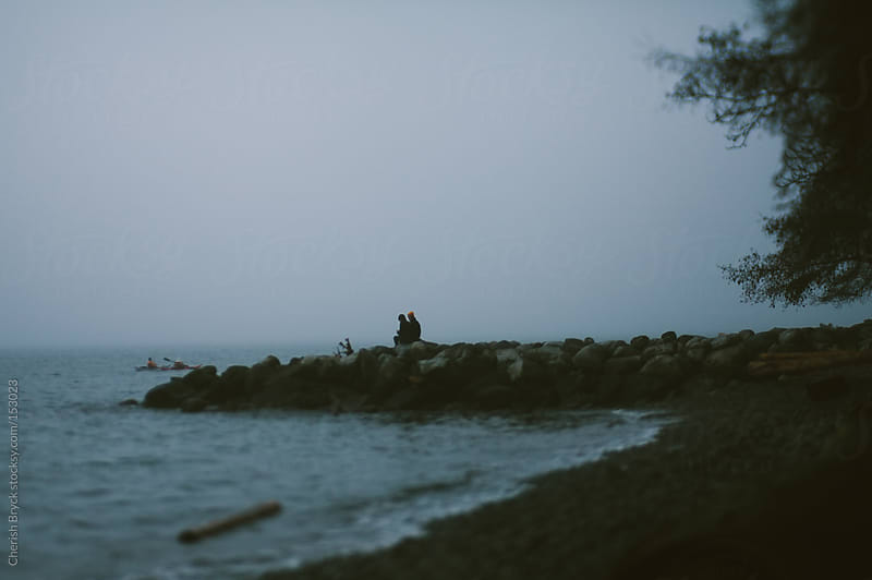 Two people walk out on the rocky beach to be alone. by Cherish Bryck for Stocksy United