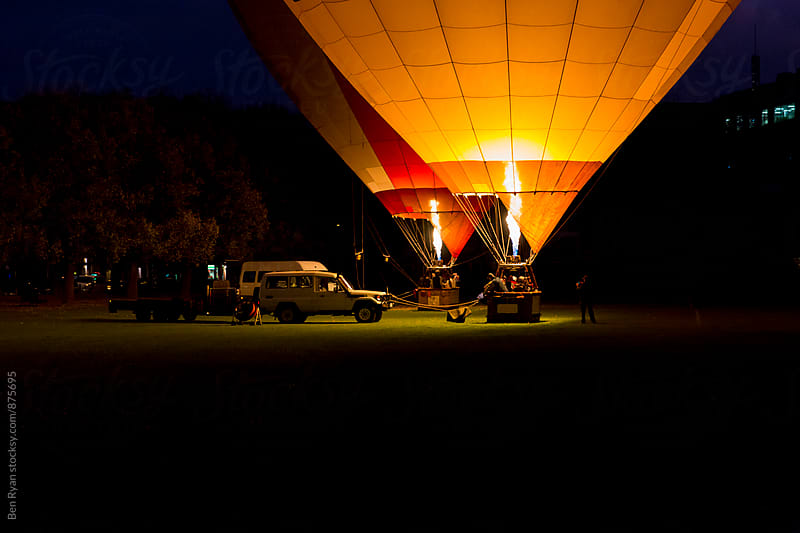 Two hot air balloons being inflated in early dawn by Ben Ryan for Stocksy United