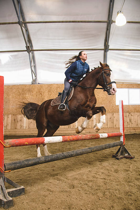 Young woman on horse jumping over hurdle by Danil Nevsky for Stocksy United