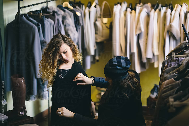 Woman wearing a jersey with the help ofshop assistant by michela ravasio for Stocksy United