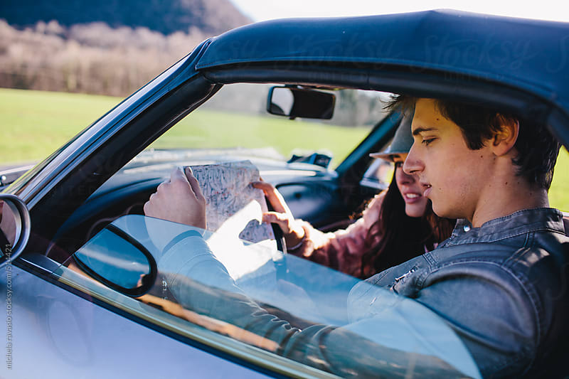 Young couple looking at the road map in the car by michela ravasio for Stocksy United
