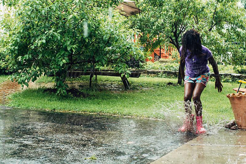Black girl jumping in puddle by Gabriel (Gabi) Bucataru for Stocksy United