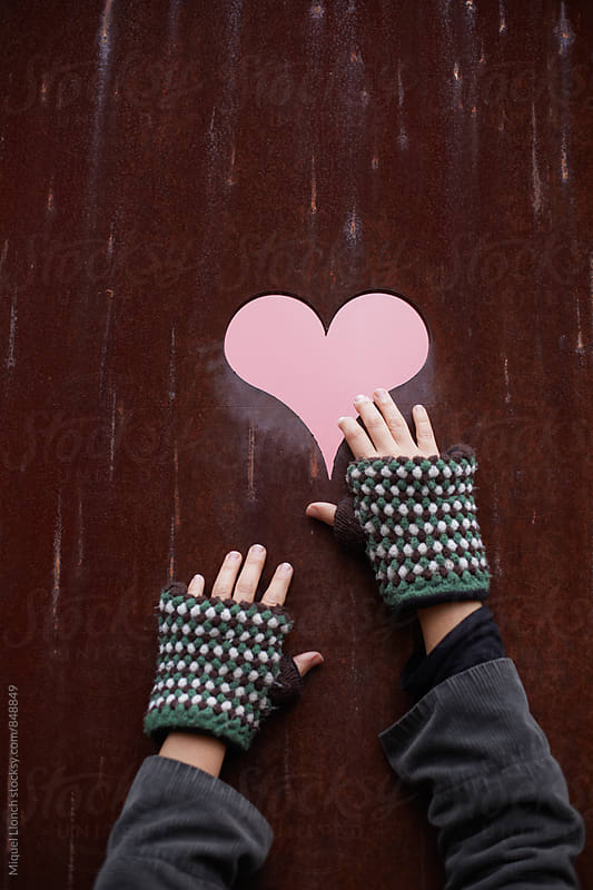 Woman hands reaching a pink heart by Miquel Llonch for Stocksy United