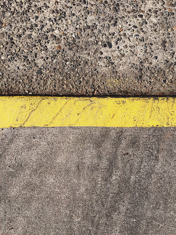 Painted yellow curb bordering sidewalk and street by Paul Edmondson for Stocksy United