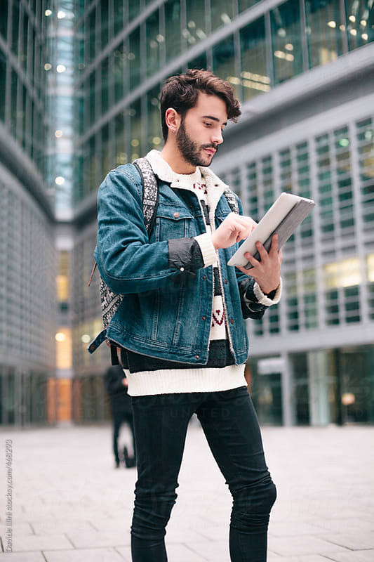 Young man using a digital tablet by Davide Illini for Stocksy United