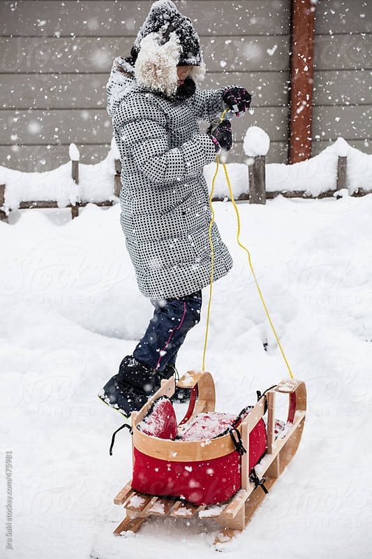 girl playing sled on snow by jira Saki for Stocksy United