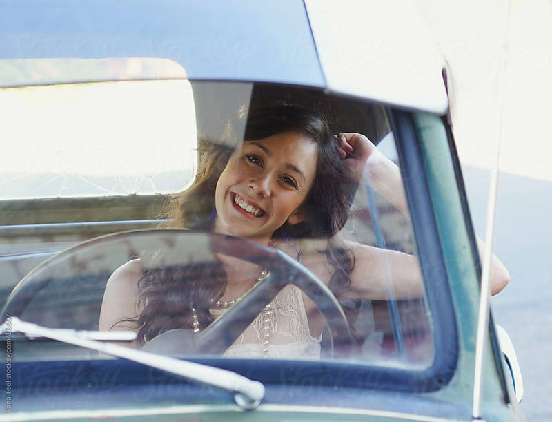 A young woman peering through front windshield of old pickup.  by Tana Teel for Stocksy United