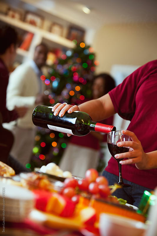 Christmas: Party Guest Pouring Wine by Sean Locke for Stocksy United
