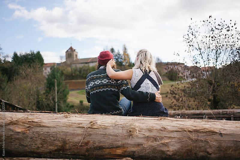 Embraced couple in love sitting on a large tree trunk. by Koen Meershoek for Stocksy United