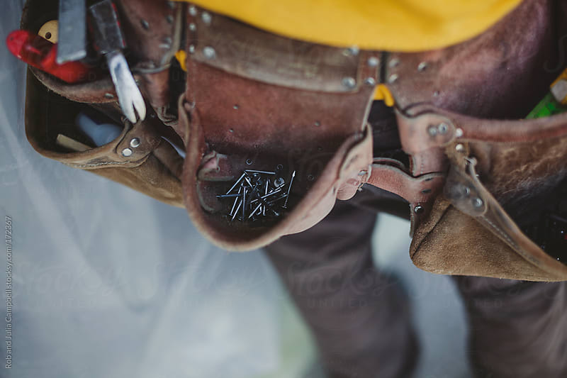 detail of nails in carpenters tool belt by Rob and Julia Campbell for Stocksy United