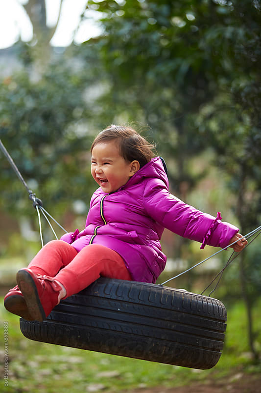 happy little asian girl sitting on the swing by Bo Bo for Stocksy United