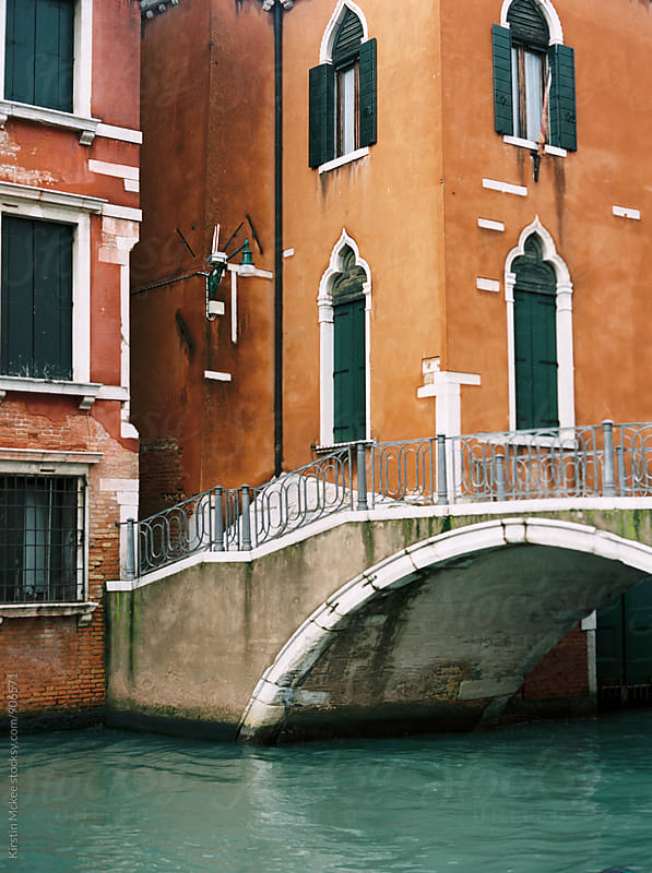 Orange and pink buildings in Venice with bridge by Kirstin Mckee for Stocksy United