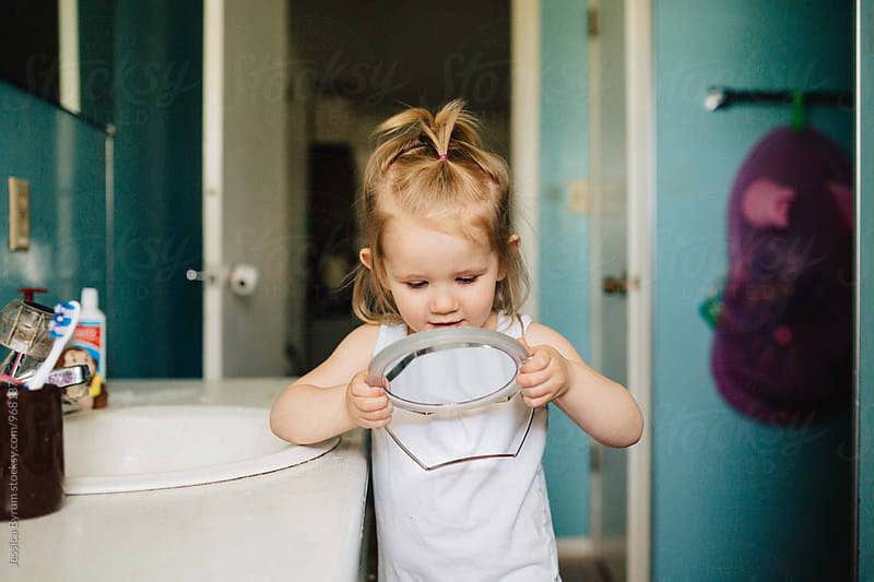 Toddler girl looking into small mirror by Jessica Byrum for Stocksy United