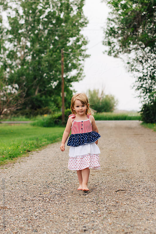Toddler girl walking barefooted down a gravel driveway. by Jessica Byrum for Stocksy United