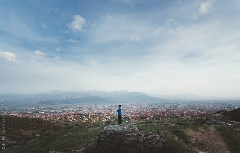 Child taking a view of city. by Dejan Ristovski for Stocksy United