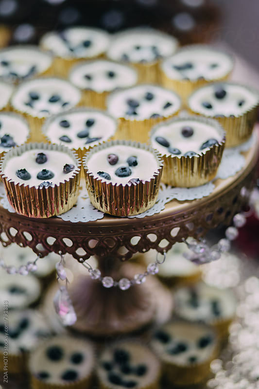 Blueberry cream tarts on cake stand by ZOA PHOTO for Stocksy United