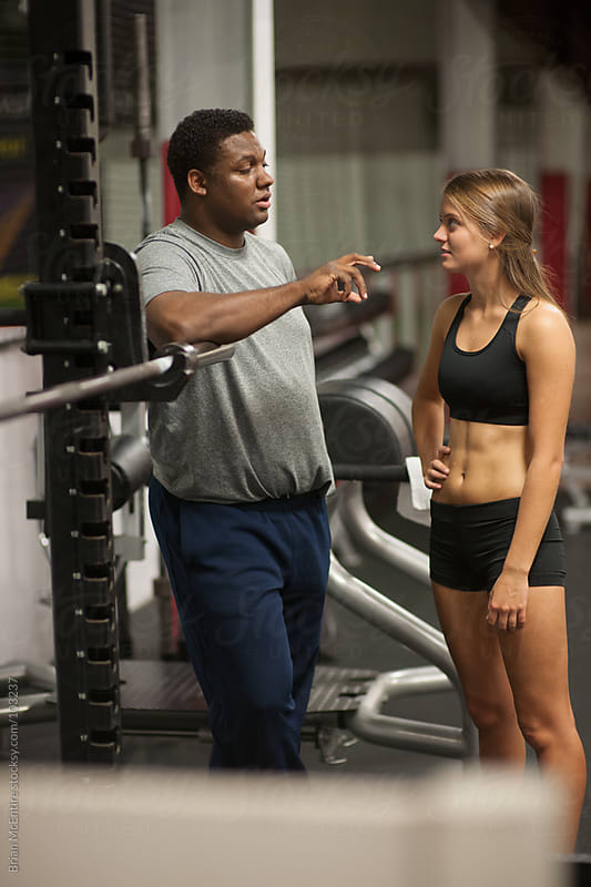 Trainer and Athlete Talk about Workout in Gym by Brian McEntire for Stocksy United
