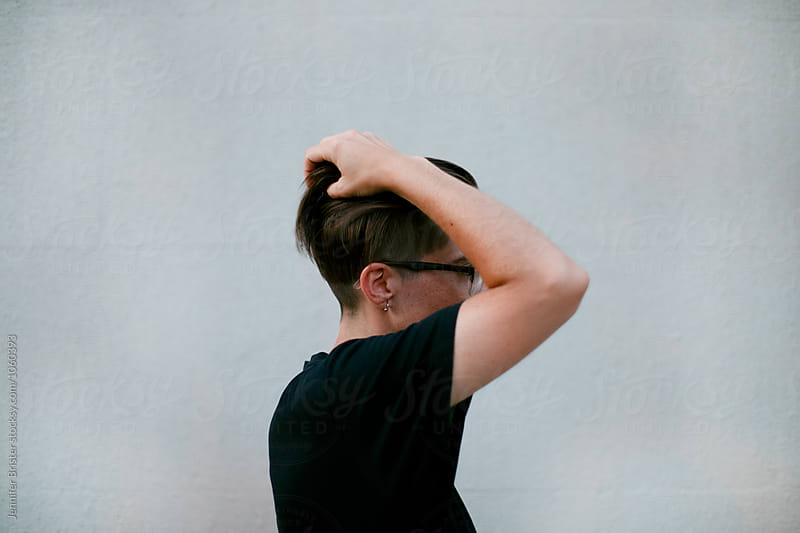 Woman running hand through short, awesome haircut by Jen Brister for Stocksy United