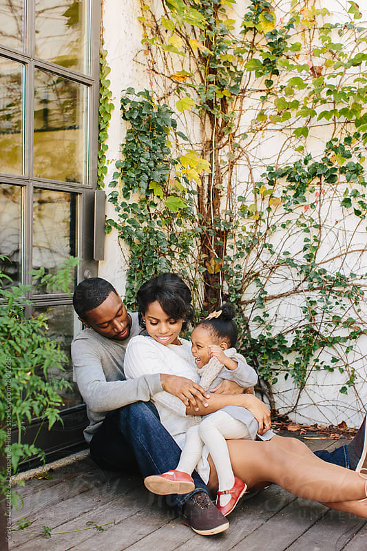 A beautiful family of three snuggled up together outdoors.  by Kristen Curette Hines for Stocksy United