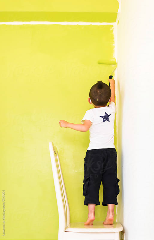 Kid painting the wall of his room from white to light green by Lawren Lu for Stocksy United