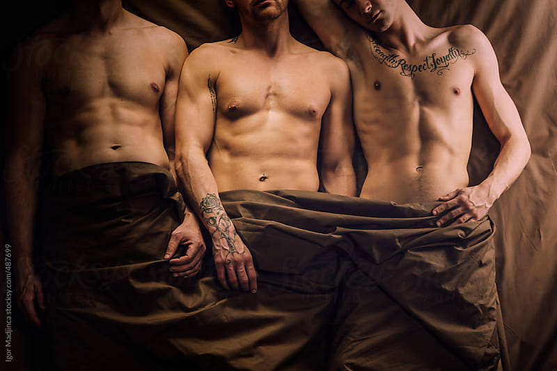 gay tattooed couple and friend in bed, sleeping by Igor Madjinca for Stocksy United