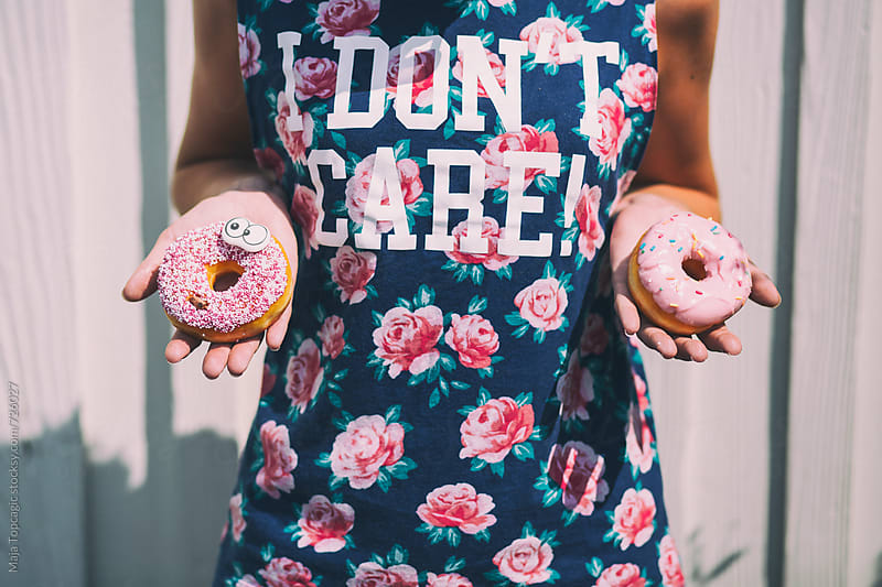 Young beautiful brunette eating a donut by Maja Topcagic for Stocksy United