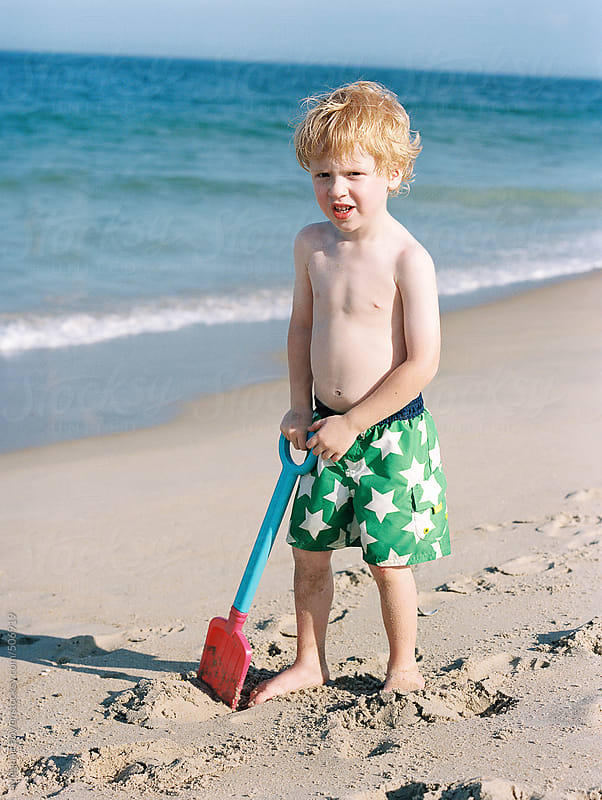 boy playing with a  shovel on the beach by Meghan Boyer for Stocksy United