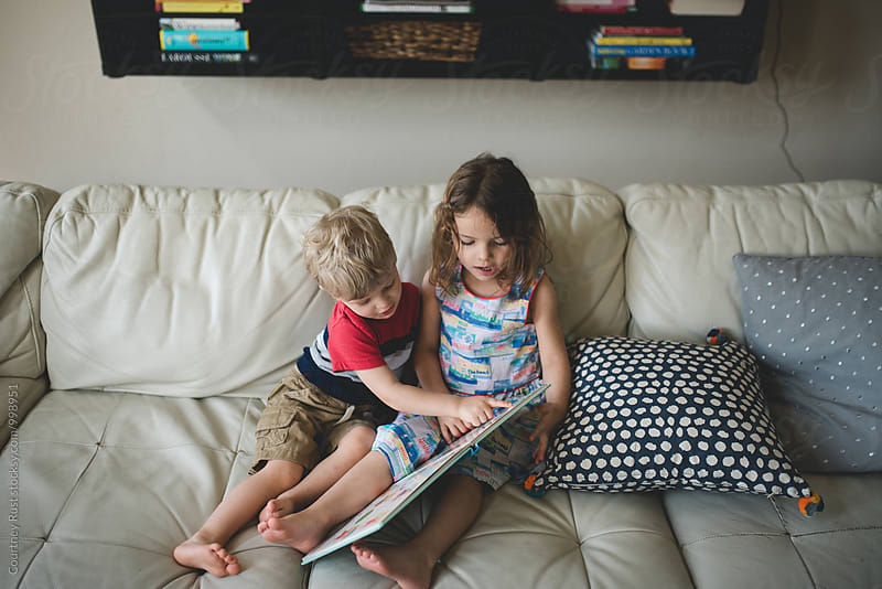 Two Children (siblings) reading at home by Courtney Rust for Stocksy United