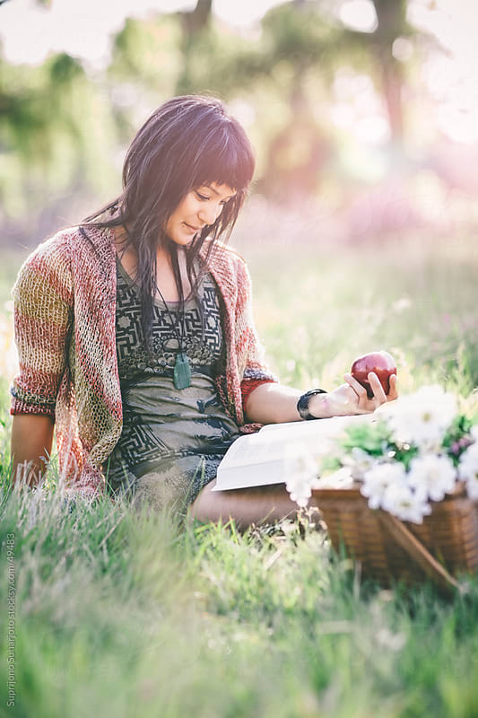 Beautiful woman reading a book on a grass field by Suprijono Suharjoto for Stocksy United