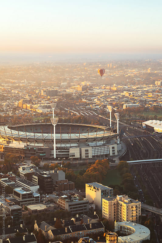 an hot air balloon floats over iconic Melbourne Cricket Ground