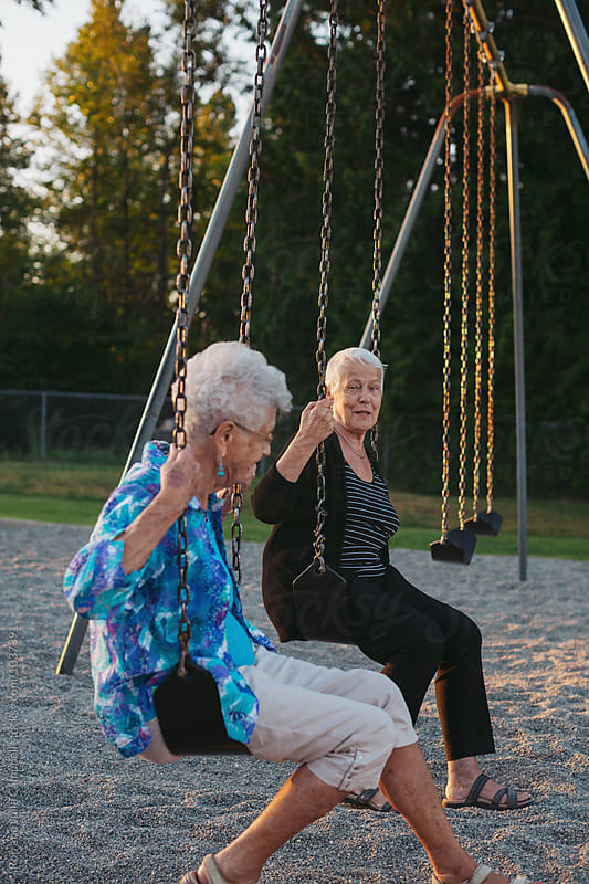 Two happy, senior caucasian friends swinging together on swingset at sunset by Rob and Julia Campbell for Stocksy United