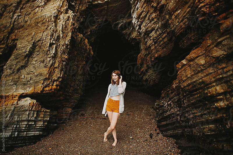 girl next to sea cave by Dylan M Howell Photography for Stocksy United