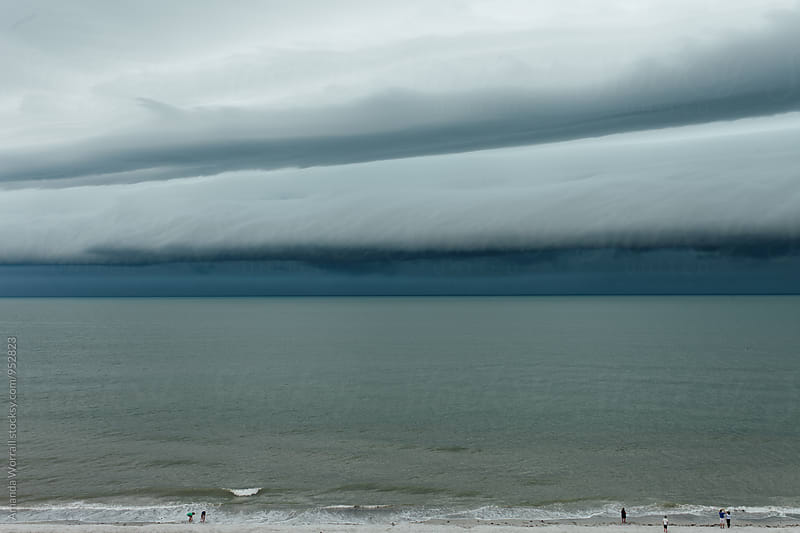 People on beach watching a tropical storm come in by Amanda Worrall for Stocksy United