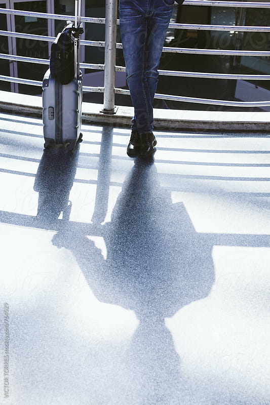 Shadow of a Businessman with Luggage at the Airport by VICTOR TORRES for Stocksy United