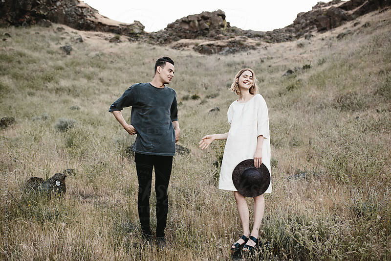 modern fashionable couple standing laughing in desert  by Nicole Mason for Stocksy United