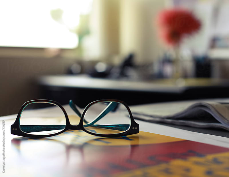 Glasses on someone's desk in the office by Carolyn Lagattuta for Stocksy United