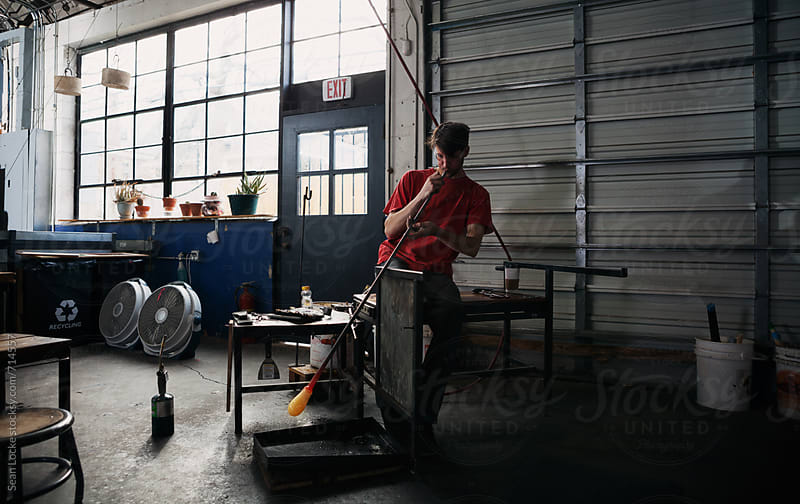 Glass: Man Using Blowpipe to Shape Molten Glass by Sean Locke for Stocksy United