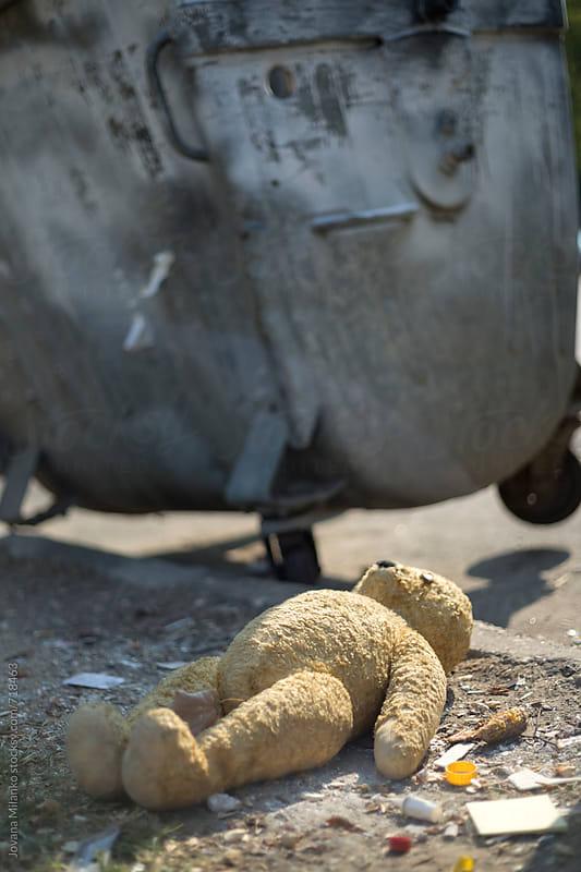 Broken teddy bear next to a dumpster by Jovana Milanko for Stocksy United