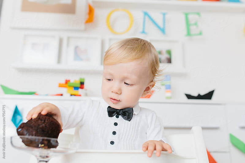 One year old child with bow tie grabs at cupcake by Amir Kaljikovic for Stocksy United