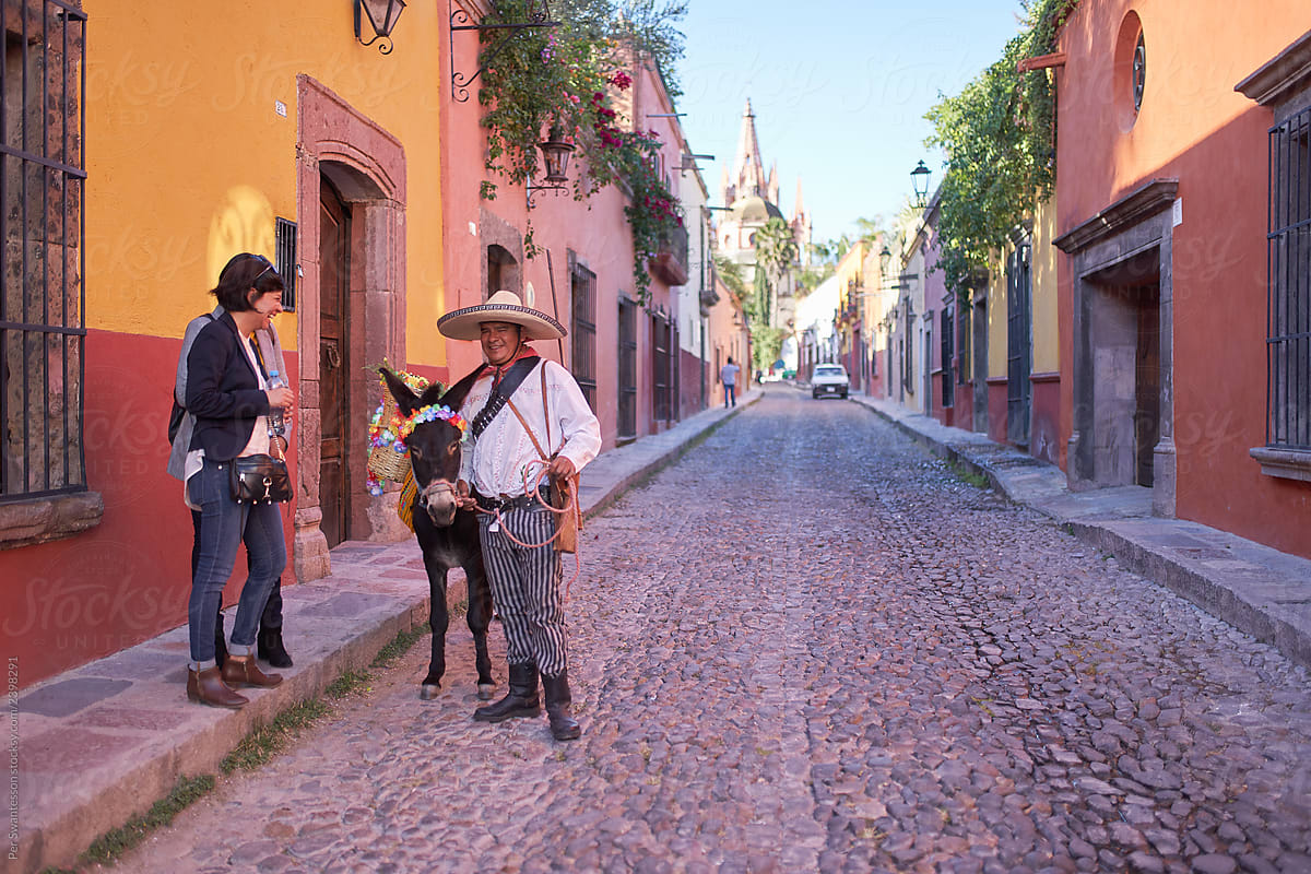 Image result for Tourists talking to a traditionally dressed Mexican man with a donkey in San Miguel de Allende